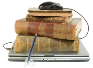 Photograph of laptop with old books and computer mouse on top representing old and new
